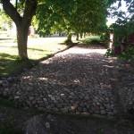 """Ett """"dike"""" skall grävas ur och fyllas med dränerande material runt stenläggningen."""